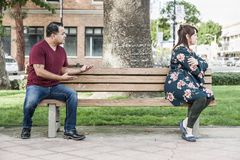 Arguing Mixed Race Couple Sitting Facing Away From Each Other on Park Bench. Unhappy Mixed Race Couple Sitting Facing Away From Each Other on Park Bench royalty free stock photo