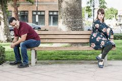 Arguing Mixed Race Couple Sitting Facing Away From Each Other on Park Bench stock photography