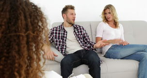 Arguing young couple sitting on couch