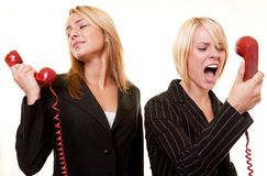 Argument over the phone. Two business women one yelling into the receiver the other holding the phone away from ear to show a loud argument Royalty Free Stock Photography