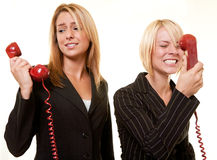 Argument over the phone. Two business women one yelling into the receiver the other holding the phone away from ear to show a loud argument Stock Photo