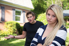The argument. A young women glares at the camera while her boyfriend gestures angrily in the background Stock Photography