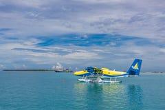 12 09 2015: Ari opłata drogowa, Maldives: Hydroplanu lądowanie w ocean lagunie Start hydroplan od ocean plaży obrazy royalty free