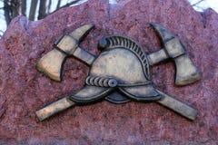 Aria aperta, architettura urbana, elemento del monumento ai vigili del fuoco, casco, asce, rame immagini stock