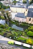 Arial-Ansicht von Grund-Bezirk von Luxemburg-Stadt gesehen mit Neumuenster Abtei-, Alzette-Fluss und grünem touristischem Zug Lizenzfreie Stockbilder