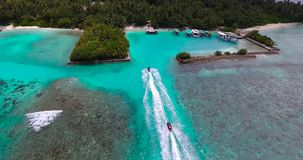 Arial drone shot of two jet skis driving into the harbor. On the maldives stock video