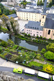 Arial view of Grund district of Luxembourg City seen with Neumuenster Abbey, Alzette river and green touristic train Royalty Free Stock Images