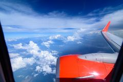 Clouds in the sky and cityscapes though airplane window. Red aeroplane flying. Arial view from internal cabin of aeroplane.Clouds in the sky and cityscapes stock images
