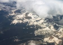 Arial view looking down on snow covered mountains shrouded with fog. An Arial view looking down on snow covered mountains shrouded with fog stock photos