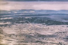 Arial view of snow covered terrain with mountains in the distance and a few low clouds over a river and a town and a highway somew. Here in the Rocky Mountains royalty free stock image