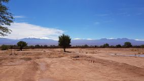 The arid and desolate landscape of the Atacama Desert with the peaks of the snowy volcanoes of the Andes cordillera. The arid and desolate landscape of the stock image