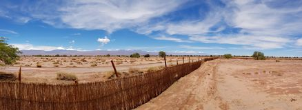 The arid and desolate landscape of the Atacama Desert and the peaks of the snowy volcanoes of the Andes cordillera in the backgrou. Nd stock photography