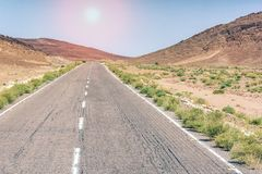 An arid hot desert with mountains and a road under a blue sky royalty free stock photo