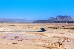 An arid hot desert with mountains and a road under a blue sky stock images