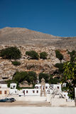 Arid lanscape in Lindos. At the arrival in Lindos this was the first scenary we saw: arid hills and white architecture on a excesive blue sky stock photography