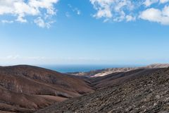 Arid rolling landscape with ocean in background under blue sky on Fuerteventura. Island Stock Image