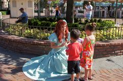 Ariel. From the movie The Little Mermaid laughing with some children at the entrance of Disneyland in California Stock Photos