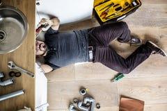 Ariel view man fixing kitchen sink royalty free stock photo