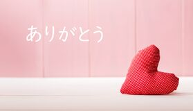 Arigato - Thank you in Japanese language with a red heart cushion