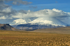 Arinacota and Pomerape volcanoes. View of snow-capped Parinacota and Pomerape volcanoes known as Payachatas, Chile Royalty Free Stock Photography