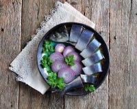 Aringa salata deliziosa con la cipolla rossa, il sale ed il pepe sui vecchi precedenti di legno Stile rustico Fotografia Stock