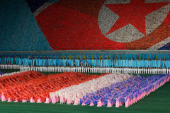 Arirang Mass Games 2011 in DPRK. Tribune showing a the North Korean flag and female dancers on the ground in the colors of the flag. The tribune picture is Stock Photo