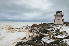 Arisaig Lighthouse frozen ocean Nova Scotia Canada. Frozen Atlantic Ocean off seashore at Arisaig Lighthouse in Antigonish County, Nova Scotia, NS, Canada royalty free stock images