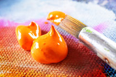 Aristic acrylics paint. Professional acrylics orange paint on canvas with brush stock images