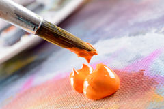 Aristic acrylics paint. Professional acrylics orange paint on canvas and loaded brush stock photography