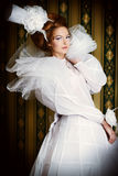 Aristocracy. Beautiful fashion model in the refined white dress and elegant hat. Vintage style. Art project stock photo