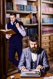 Aristocracy and education concept. Man with beard typing on typewriter. While his friend reading book on background. Men in oldfashioned suits, professors stock image