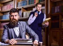 Aristocracy and elite concept. Man with beard and strict fac. E near typewriter while his friend reading book on background, defocused. Men in suits, professors royalty free stock image