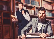 Aristocracy and elite concept. Man with beard and strict fac. E near typewriter while his friend reading book on background, defocused. Men in suits, professors royalty free stock images