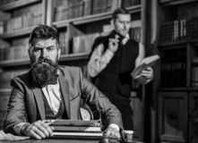 Aristocracy and elite concept. Man with beard and strict fac. E near typewriter while his friend reading book on background, defocused. Men in suits, professors stock photos