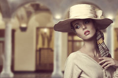 Aristocratic girl with hat. Fashion girl with big elegant hat and foulard on the head posing with beige dress and sensual expression Stock Photo