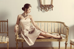 Aristocratic girl on sofa. Interior portrait of brunette elegant girl lying on retro sofa in aristocratic room. Wearing pink dress, precious jewellery and Royalty Free Stock Photos