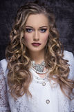 Aristocratic old fashion girl. Fashion portrait of splendid blonde curly woman with vintage elegant white clothes, precious necklace and stylish make-up Stock Photography