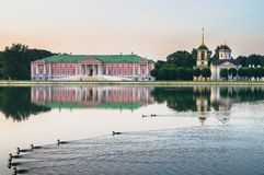 Aristokratisk herrgård och kyrka med klockatornet bredvid dammet i museum-godset Kuskovo, Moskva royaltyfri fotografi