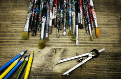 Aritst's desk with old paintbrushes and colored pencils. Stock Photos