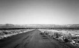 Arizona desert highway. Black and white scenic view of highway in Arizona desert with west rim of Grand Canyon in background, U.S.A Royalty Free Stock Photo