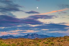Arizona Desert Sunset. Arizona sunset with mountains in the background and sagebrush in the foreground with moon in the sky stock photos