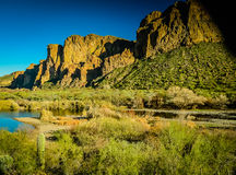 Arizona Desert. Superstition Mountains bathed in golden afternoon light with azure blue river at base Stock Photo