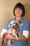 Arizona Humane Society Volunteer and Puppy. A smiling Arizona Humane Society woman volunteer holds a young pup that is up for adoption royalty free stock images