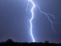 Arizona Monsoon Lightning 2009. A massive lightning bolt striking behind a home in Arlington Arizona during the 2009 Monsoon season. This bolt struck less than Stock Photos