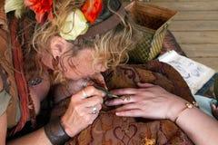 Arizona Renaissance Festival Tattoo. Arizona Renaissance Festival artist paints a tattoo on visitor`s hand stock photos