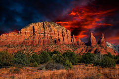 Arizona, Sedona, Cathedral Mountain Sunset. Thundering sunset clouds of red and dark blues pass over the peak of Cathedral mountain range, turning the landscape Stock Photo