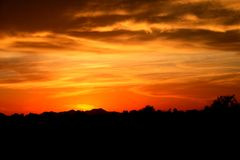 Arizona Sunset. The sun sets low in Arizona which causes the sand in the air to give it a beautiful redish orange color royalty free stock photography