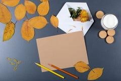 Ark av brunt hantverkpapper, vitt kuvert med hote och blomma, arkivbild