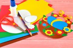 Ark av kulört papper, sax, lim, blyertspennan, påskkorgen och ägg - ställ in för barnkonst royaltyfri foto