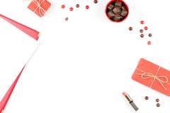 Ark av papper, chokladsötsaker, gåvaask, läppstift Kvinnlig bakgrundsram i rött och vitt Lekmanna- lägenhet, kopieringsutrymme Arkivbild